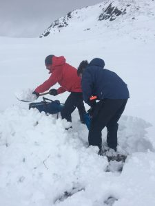 ready2climb: two walkers digging snow to create a temporary lunchtime shelter