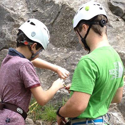 ready2climb: a qualified instructor helps a oung climber tie in before climbing outdoors