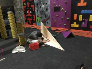 ready2climb: a worker fixing T nuts to th rear of a climbing volume